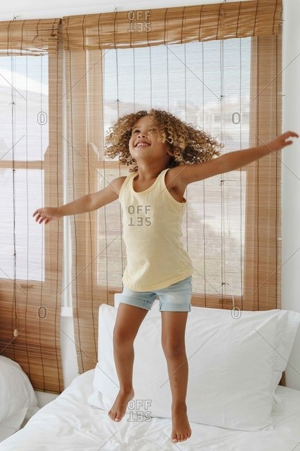 Little girl jumping with arms open on bed in beach house