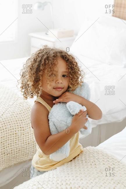 Little girl cuddling soft toy in bedroom