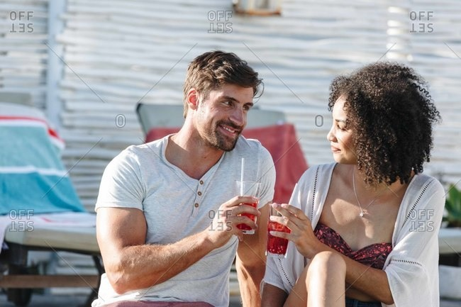 Couple enjoying iced drink by swimming pool