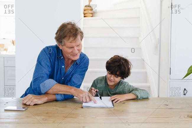 Father helping son with homework at home