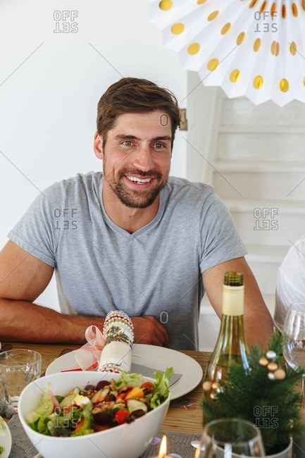 Man listening at dining table in home party