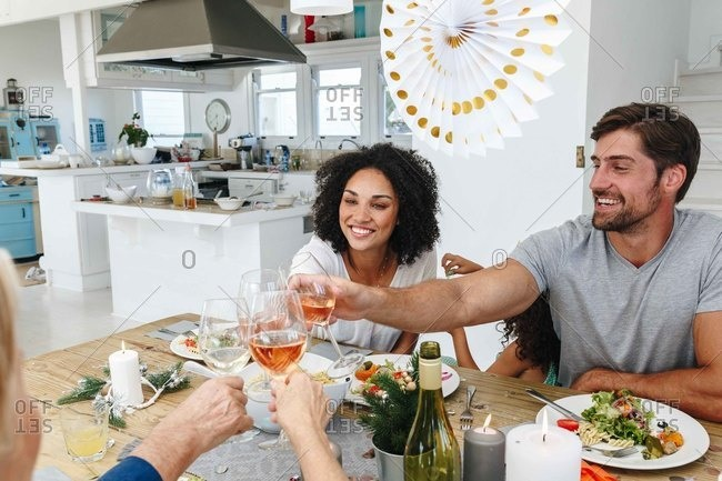 Family toasting wine at dining table in home party