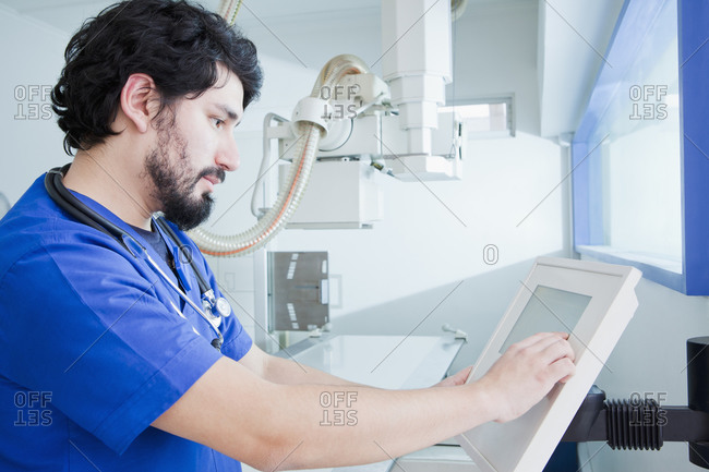 Young male radiographer operating X-ray machine control panel in radiology department