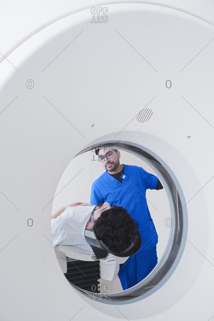 Young male radiographer operating  CT scanner in radiology department