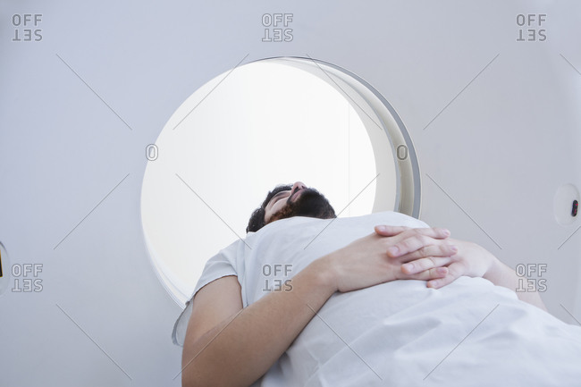 Young male patient having a CT scan in radiology department