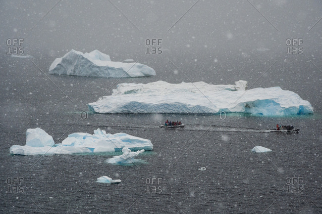 Tourists in inflatable boat sailing past icebergs in snowstorm, Portal Point, Antarctica