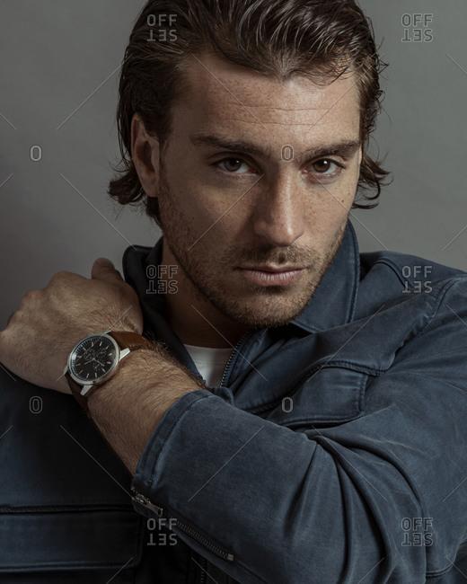Man resting hand on shoulder showing off watch, grey background
