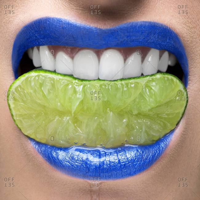 Blue lips biting on lime slice