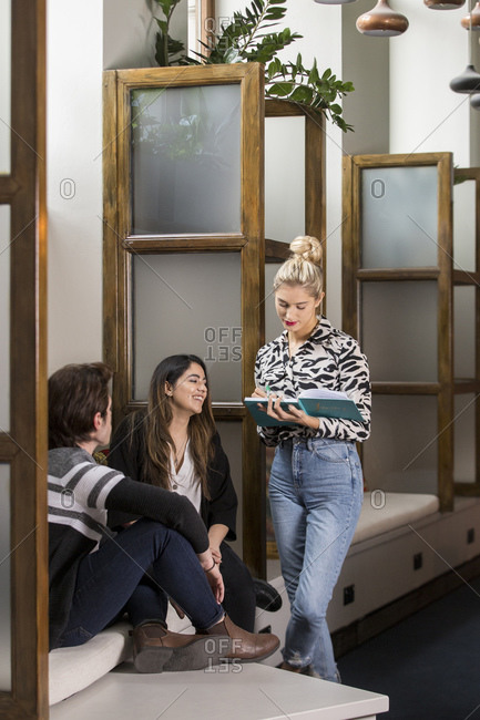 Colleagues in meeting at co-working space, three people chatting.