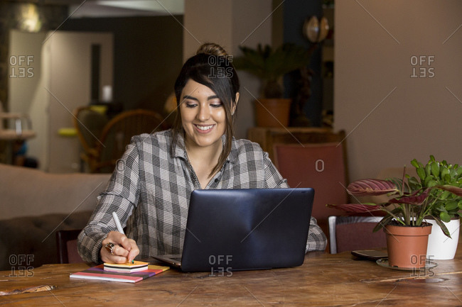 Woman writing notes and working on laptop in co-working space