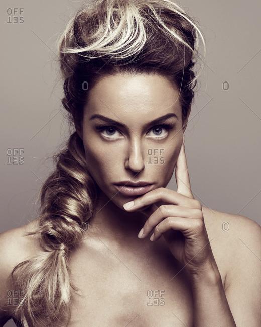 Beautiful young woman baring shoulders and touching cheek