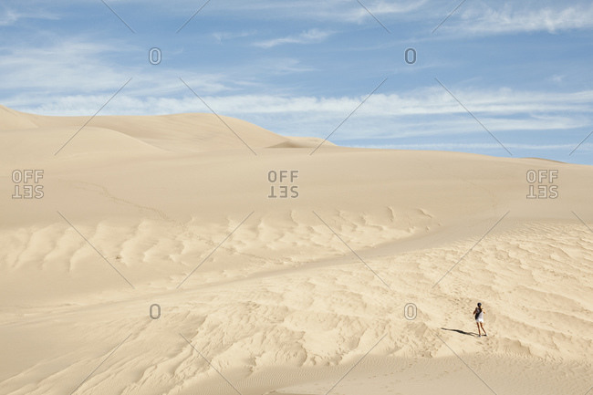 Hiker exploring sand dunes, Great Sand Dunes National Park and Preserve, Colorado, USA