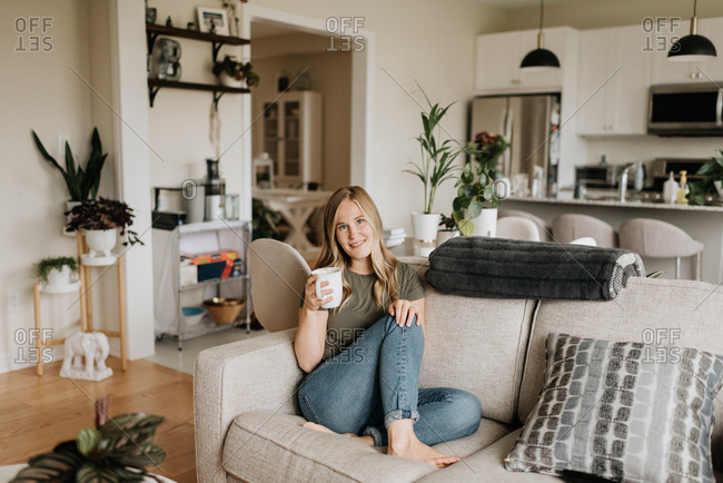 Woman relaxing on sofa with warm beverage