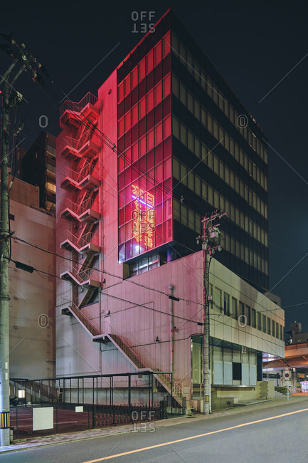 June 1, 2019: Red light reflected on facade of office building at night, view from the street, Osaka, Japan