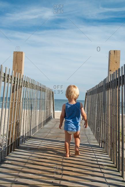 Toddler walking on boardwalk at beach