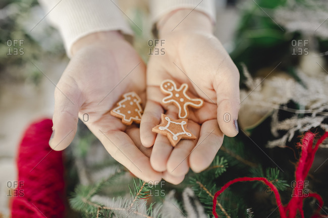 Hand holding Christmas ornaments, gingerbread man, star and tree