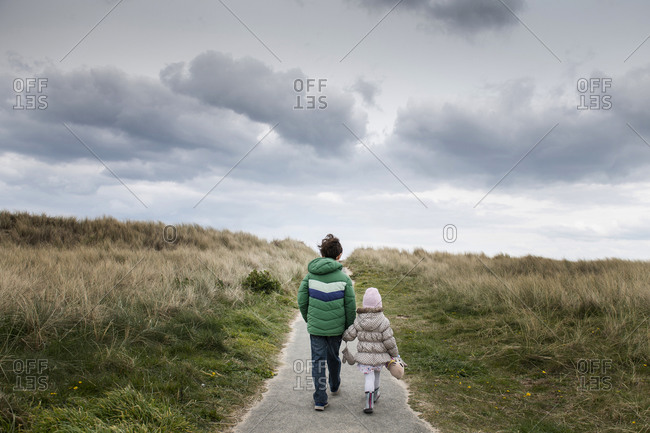 Siblings walking past field of dry grass
