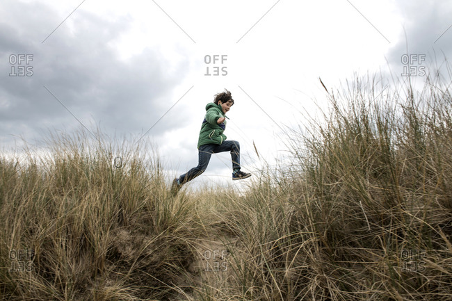 Boy jumping over dry grass on beach