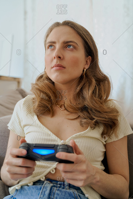 Close up of a blonde woman sitting on sofa playing video games