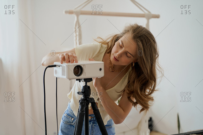 A young blond woman setting up a video projector