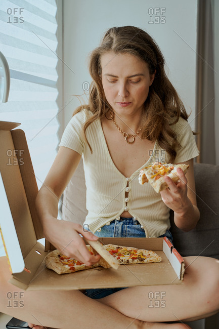 Blonde woman sitting on sofa eating pizza