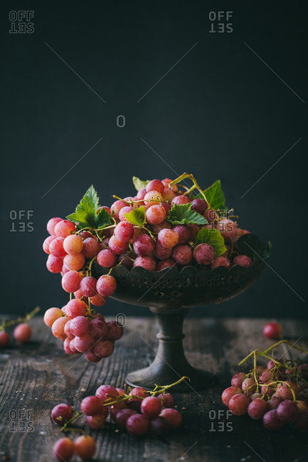Red grapes in a dish on rustic surface with black background