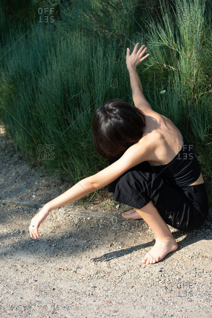 Unrecognizable young woman crouching down by tall grass and spreading her arms