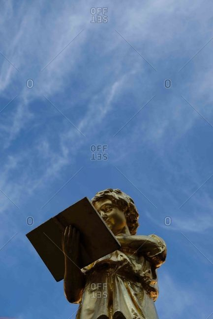 Weimar, Germany - March 1, 2019: Gold statue of child reading a book in front of the music school Johann Nepomuk Hummel