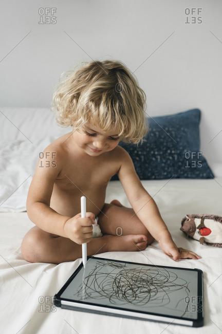 Toddler boy doodling on tablet