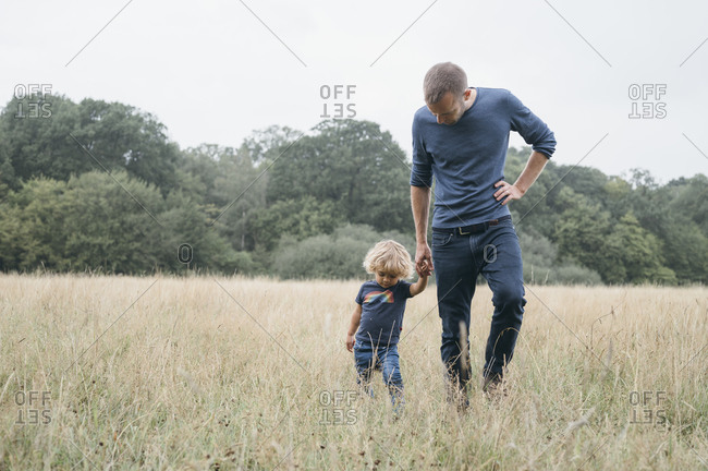 Father holding hand of son in field