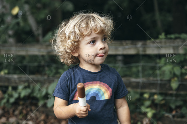 Young boy holds an ice cream bar in the forest