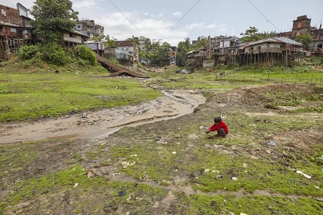 Rangamati, Bangladesh - May 5, 2013: Young girl playing in the slums of Bangladesh