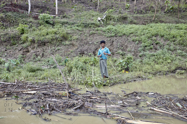 Bandarban, Bangladesh - May 6, 2013: Young Marma tribal man standing on the shore of the Sangu River