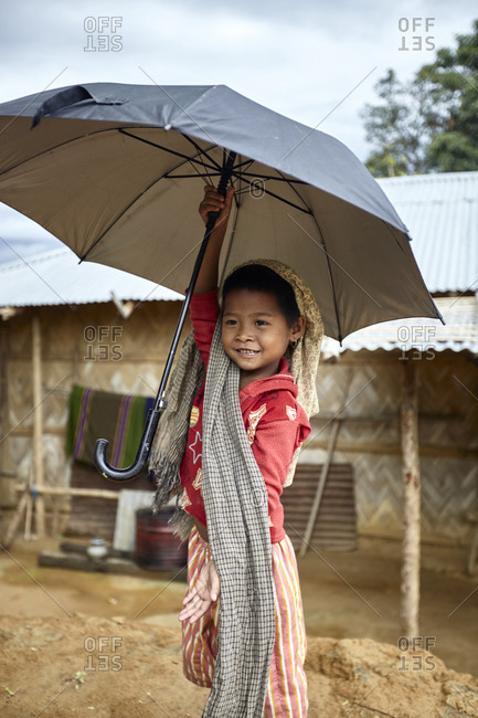 Bandarban, Bangladesh - May 6, 2013: Portrait of a young Tripuri girl holding an umbrella outdoors