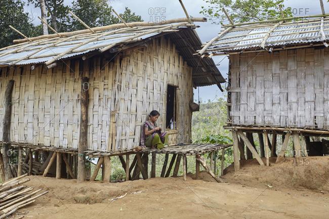Bandarban, Bangladesh - May 6, 2013: A Tripuri woman sitting outside of a bamboo hut