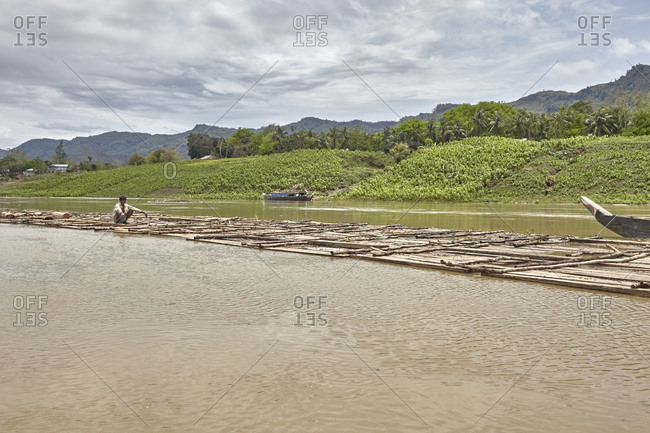 Bandarban, Bangladesh - May 6, 2013: Man on floating bamboo rafts on the River Sangu