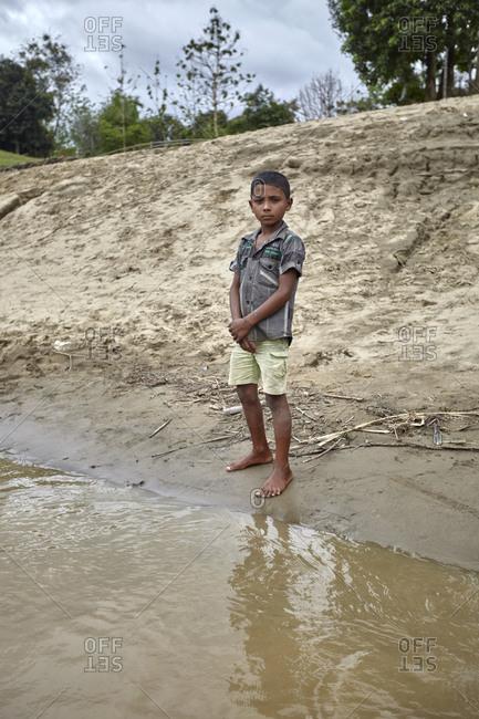 Bandarban, Bangladesh - May 6, 2013: Young boy standing on the banks of the River Sangu