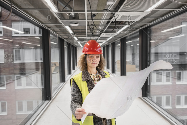 Female worker looking at blueprints