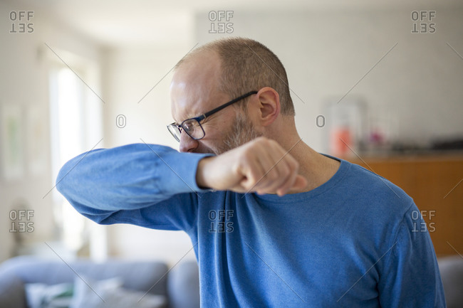 Man sneezes into his elbow