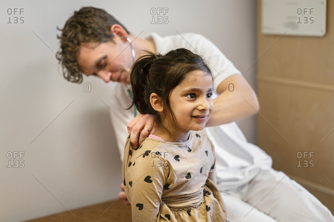 Doctor examining girl in his office