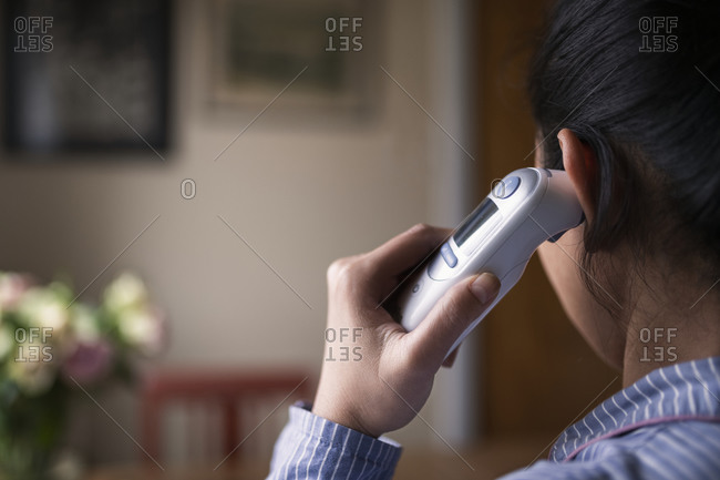 Woman checking her temperature at home