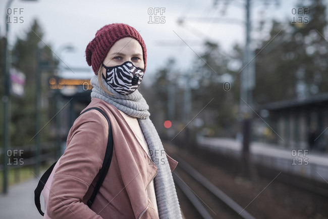 Woman with face mask waiting for public transportation