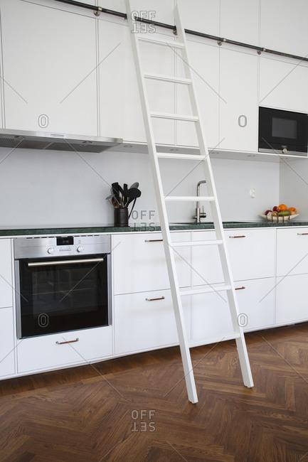 Ladder against cupboards in kitchen