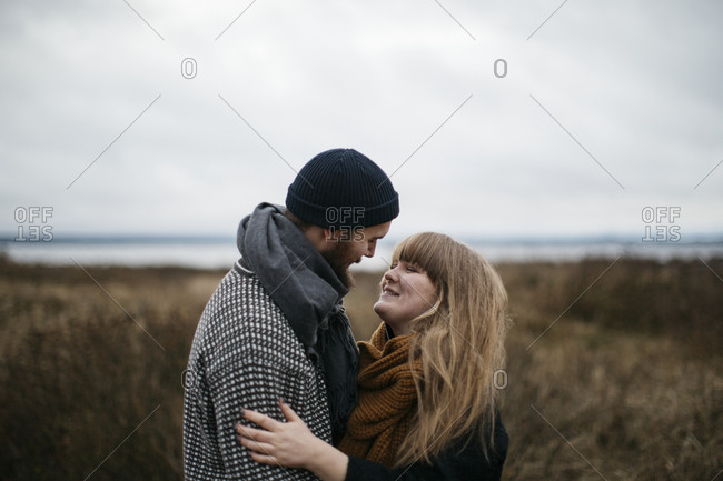 Couple standing together intimately outdoors