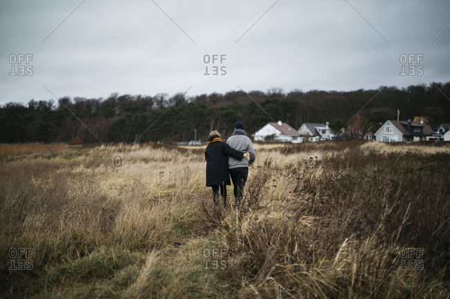 Couple walking through meadow together