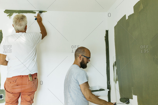 Men painting walls of their home