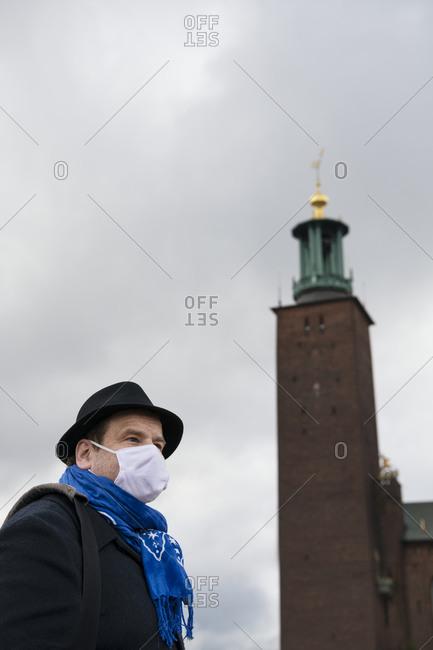 Man wearing protective mask, Stockholm City Hall in background, Stockholm, Sweden