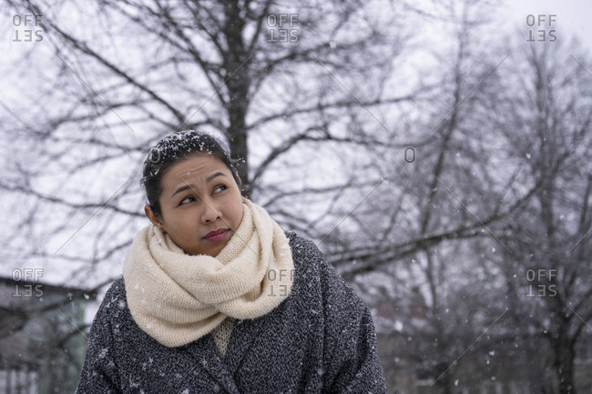 Woman looking up at falling snow