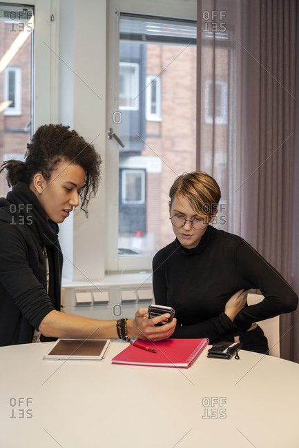 Colleagues at work meeting looking at phone