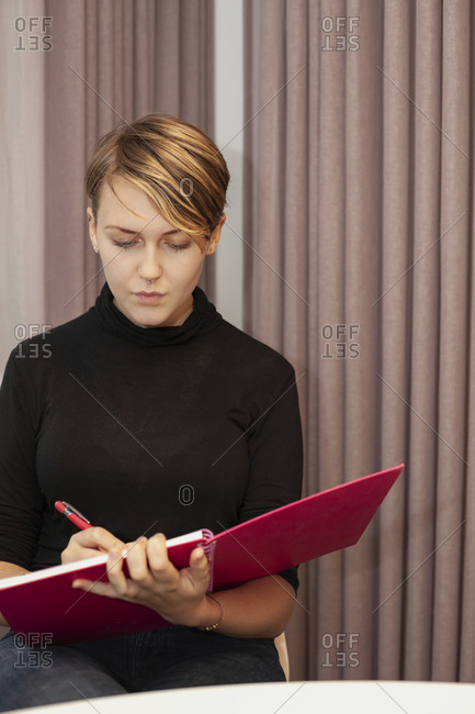 Woman at work meeting doing notes